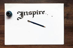 Calligraphy handmade lettering background. Flat lay. Inspire word drawn with inks on sheet of paper. Drawing lessons, art school, creativity, writing concept Stock Photo