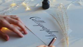 Calligraphy inscription with nib pen ant black ink. Written word calligraphy with broad nib pen. Lettering with black ink and twinkling garlands. Concept of art stock footage
