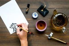 calligraphy La mano escribe amor del jeroglífico en el Libro Blanco en la opinión de top de madera oscura del fondo imagen de archivo libre de regalías