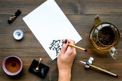 calligraphy La mano escribe amor del jeroglífico en el Libro Blanco en la opinión de top de madera oscura del fondo fotos de archivo