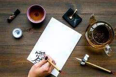 calligraphy La mano escribe amor del jeroglífico en el Libro Blanco en la opinión de top de madera oscura del fondo imágenes de archivo libres de regalías