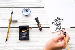 calligraphy La mano escribe amor del jeroglífico en el Libro Blanco en la opinión superior del fondo de madera fotografía de archivo