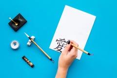 calligraphy La mano escribe el jeroglífico en el Libro Blanco en espacio azul de la copia de la opinión superior del fondo imagenes de archivo