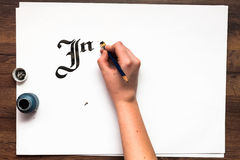 Calligraphy lettering. Artist workplace top view. Unrecognizable painter`s hand drawn word inspire with ink on white paper background. Drawing lessons, art royalty free stock images