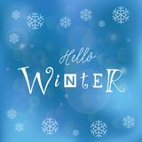 Calligraphy lettering of Hello winter with different letters on blue background decorated with snowflakes Royalty Free Stock Photo