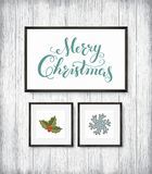 Calligraphy Lettering MERRY CHRISTMAS with hand drawn elements in frames on wooden wall. Calligraphy Lettering MERRY CHRISTMAS poster with hand drawn elements Royalty Free Stock Image