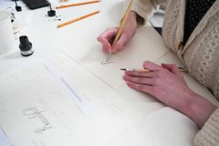 Calligraphy lettering workshop. Young women`s hand, writting let royalty free stock image