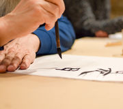 Calligraphy master drawing chinese hieroglyph Royalty Free Stock Photos