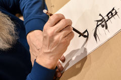 Calligraphy master drawing chinese hieroglyph. With a brush Stock Images