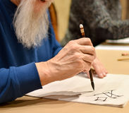 Calligraphy master drawing chinese hieroglyph. With a brush Stock Image