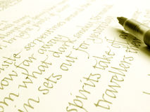Calligraphy pen and hand writing. An image showing a modern type of calligraphic manuscript pen, placed over a sample of calligraphy practise writing stock image