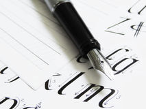 Calligraphy pen, letters. In a book stock image