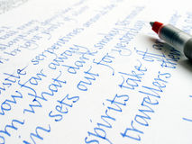 Calligraphy pen and writing on paper. An image showing a modern type of calligraphic manuscript pen, placed over a sample of calligraphy practise writing royalty free stock photo