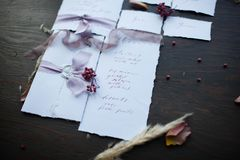 Calligraphy and printing of manual work. Graphic arts of beautiful wedding calligraphy cards with flower and chiffon bobbins on wood background. Beautiful Royalty Free Stock Photos