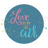 Calligraphy sign- Love is in the air in circle with multi-colored splatters. Calligraphy sign- Love is in the air in circle Stock Images
