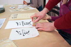 Calligraphy workshop. Chinese characters on white paper during calligraphy workshop seal royalty free stock photos