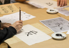 Calligraphy workshop. Person drawing Chinese characters on white paper during calligraphy workshop stock image