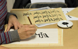 Calligraphy workshop. Person drawing Chinese characters on white paper during calligraphy workshop stock images
