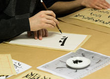 Calligraphy workshop. Person drawing Chinese characters on white paper during calligraphy workshop Royalty Free Stock Photography