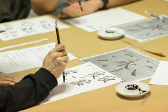 Calligraphy workshop. Person drawing Chinese characters on white paper during calligraphy workshop Stock Photo