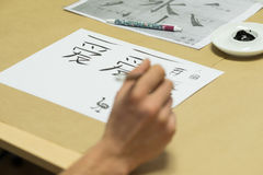 Calligraphy workshop. Person drawing Chinese characters on white paper during calligraphy workshop royalty free stock image