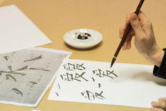 Calligraphy workshop. Person drawing Chinese characters on white paper during calligraphy workshop royalty free stock images