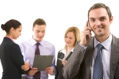 Calling. Photo of handsome employer calling his partner with working employees behind Stock Photos