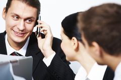 Calling. Photo of handsome employer calling his partner with colleagues near by Stock Photography