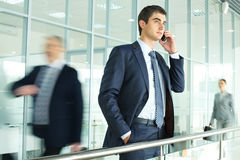 Calling. Businessman standing by banisters and calling with walking people on background stock photo