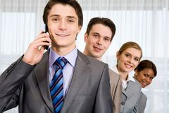 Calling. Photo of handsome employer calling his partner with successful employees behind Royalty Free Stock Photography