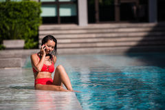 Calling all her friends to join. Portrait of a happy young woman sitting by the pool talking on her phone laughing Royalty Free Stock Image