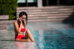 Calling all her friends to join. Portrait of a happy young woman sitting by the pool talking on her phone laughing Royalty Free Stock Photos
