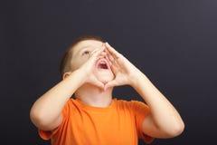 Calling aloud. Boy in orange shirt calls aloud using hands as megaphone royalty free stock photos