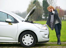 Calling for Assistance. Mature woman calling mechanic for assistance with broken down car stock photography