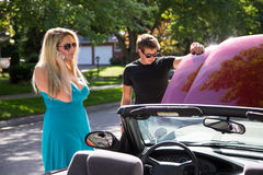 Calling for assistance. A young women stands beside a broken down car calls a tow truck or auto club for assistance as a young men checks under the hood Royalty Free Stock Photography