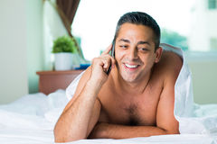 Calling in bed Stock Image