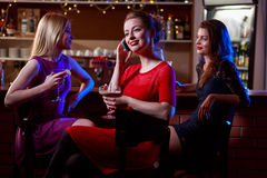 Calling best friend. Young women calling best friend from night club Stock Images