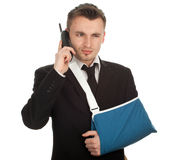 Calling businessman with broken hand Royalty Free Stock Images