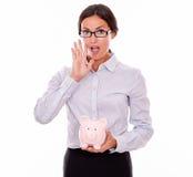 Calling businesswoman holding pink piggy bank Stock Photos
