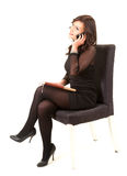 Calling businesswoman with phone sitting on chair Royalty Free Stock Image