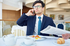 Calling in cafe. Confident leader or trader with newspaper talking on cellphone Stock Image