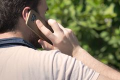 Calling with cellphone. Young guy standing outdoors calling with cellphone Stock Image