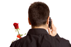 Calling for a Date. Man arranging a date via telephone and holding a rose stock photography
