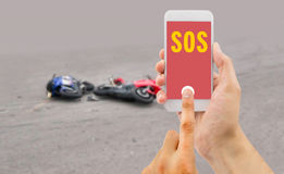 Calling emergency phone. Hand holding a cellphone with emergency number SOS on the screen with a motorcycle accident in background Stock Photography