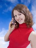 Calling from heaven. Beautiful girl talking by mobile phone in the sky Royalty Free Stock Images