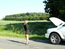 Calling for help. Blonde girl in business suit standing in middle of road on her cell phone next to broken down vehicle on the side of the road royalty free stock photography