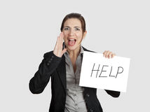 Calling for Help. Business woman calling for help holding a cardboard with the text message Help royalty free stock images