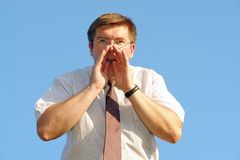 Calling for help. Young businessman calling for help over blue sky Royalty Free Stock Photography