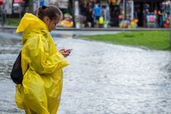 Calling for help after flood. Sarbinowo, Poland - August 2017 : Girl dresses in yellow raincoat calling for help on her mobile phone after extremely heavy royalty free stock images