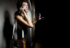 Calling 911 for Help. Woman calling 911 for help in an alley while a criminal is stalking her Royalty Free Stock Image